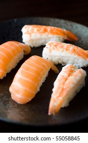 Salmon and Shrimp Sushi laid neatly on dark colored plate.