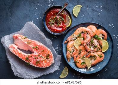 Saumon et crevettes sur assiette avec citron, sel, sauce. Concept poissons et fruits de mer. Gros plan. Vue de dessus. Grandes crevettes rouges et saumons pour le déjeuner et le dîner sur fond rustique en pierre. Alimentation saine et propre