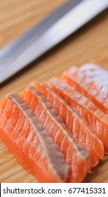 Salmon sliced for nigiri with knife in background