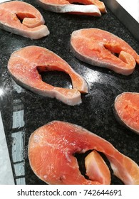 Salmon slices on black plate over crush ice  displayed in market.