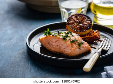 Salmon Sole Meuniere with lemon. Fillet of red fish. Steak trout fried with butter, lemon and parsley sauce.