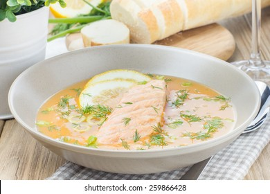 Salmon soup sprinkled with dill, served with green olives and lemons on wooden desk background
