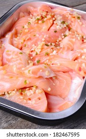 Salmon with spices on a wooden carving board