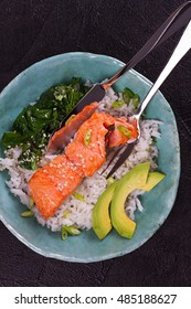 Salmon with spinach and avocado. Rice as a garnish. View from above, top studio shot