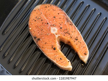 Salmon stake grilled with smoke. Salmon preparation process on grill. Grilled fish steaks on fire. Top view.