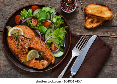 Salmon steak baked with Provencal herbs with garnish of vegetable salad on rustic, wooden stew.