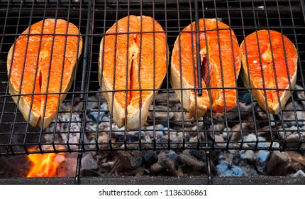 Salmon steak cooking on the BBQ grill in the summer outdoors. seafood close-up with barbecue.Top view