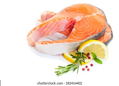 Salmon steak decorated with basil, lemon and rosemary on a white background.