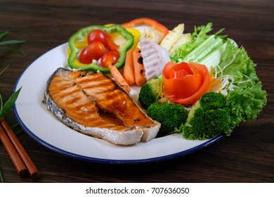 Salmon steak grilled and fresh vegetable on white plate and wooden background