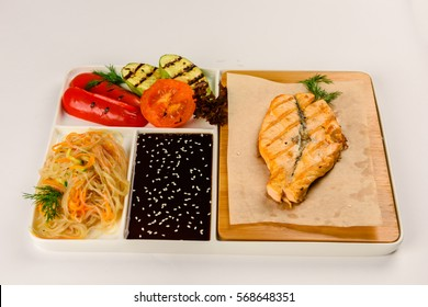 Salmon steak grilled with vegetables, rice noodles and soy sauce