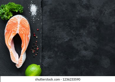 Salmon steak with lime on slate background ready for cooking. Restaurant menu, seafood recipe fish cooking on black stone background. Top view, copy space