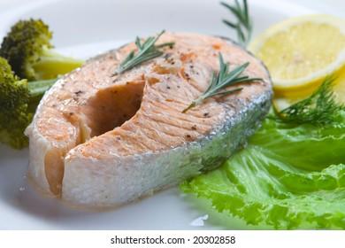 Salmon steak prepared on steam on white plate