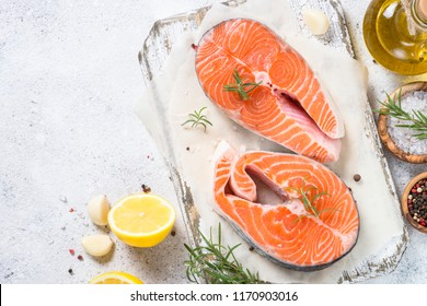 Salmon steak raw fish prepared for cooking. Top view on light stone table.