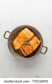 Salmon steak in roast pan on white concrete background.