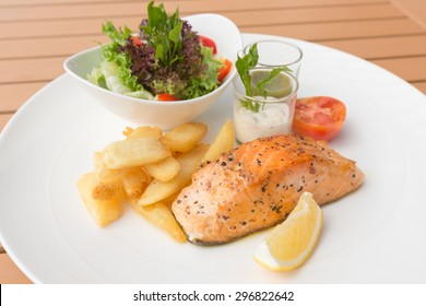 Salmon steak with salad and french fries