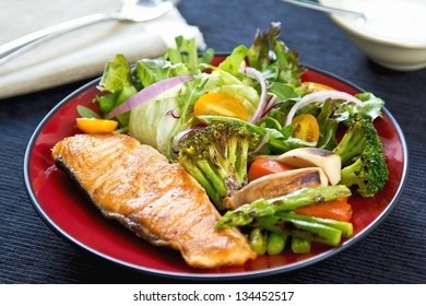 Salmon steak with sauteed vegetables and salad