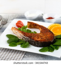 Salmon Steak with Spinach, Tomatoes and Oranges on White Plate. Square Format.