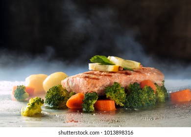 Salmon steak and steamed vegetables on tray with steam.