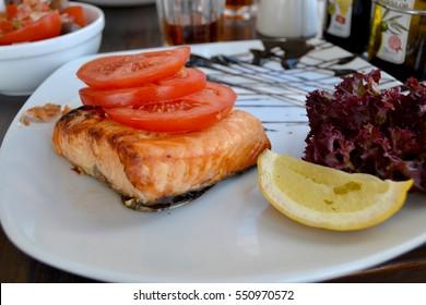 Salmon steak with tomato slices, lettuce and lemon, Malta