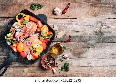 Salmon steak with vegetables on grill pan over wooden background. Top view. Raw salmon fillet with cooking ingredients: oil, herbs, spoon and fork. Banner, copy space