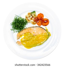 Salmon steak with yellow sauce on white plate.