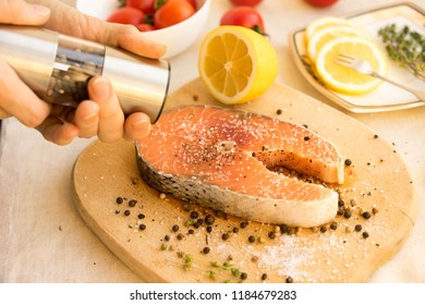 Salmon steakes with lemon on white plate
