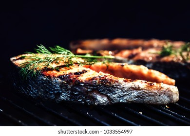 Salmon steaks cooking on barbecue grill. Food background with barbecue party
