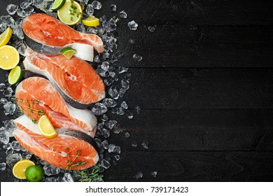 Salmon steaks on ice on black wooden table top view. Fish food concept. Copy space