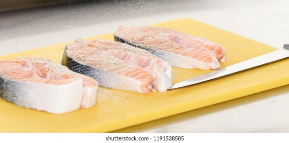 Salmon steaks sprinkled with spices on blurred background. Cutting board in yellow color with fresh salmon, flavourings and knife. Raw fish steaks ready for cooking. Salmon for cooking concept.