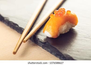 salmon sushi and chopsticks on a stone board