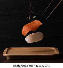 Salmon sushi floating on a black wooden background. Topped with wasabi, soy sauce and chili flakes and a pair of chopsticks