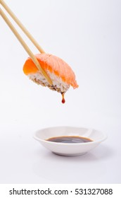 salmon sushi keep chopsticks and dipped into the sauce