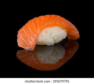 Salmon sushi nigiri over black background with reflection