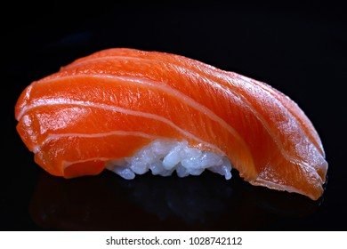 Salmon sushi on the black background, close-up, shallow focus