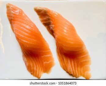Salmon sushi or pieces of raw salmon put on cooked rice in Japanese style