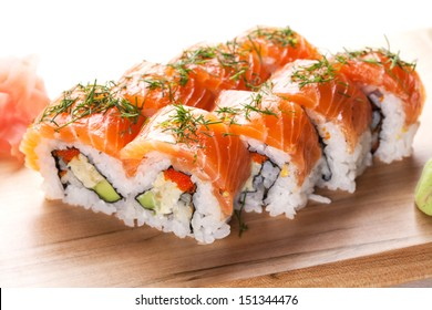 Salmon sushi rolls on wooden plate.