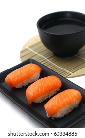 Salmon sushi served on black tray with soup