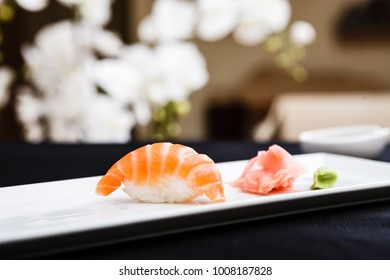 Salmon sushi served on a plate with ginger and wasabi