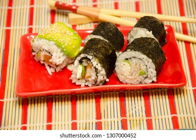 Salmon sushi set on red plate and red-stripped bamboo sheet and blurred sticks, Japanese cuisine, sea products, fine dining, Asian food