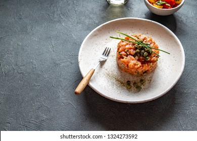 SALMON TARTAR with capers and purple onion on white plate, gray background
