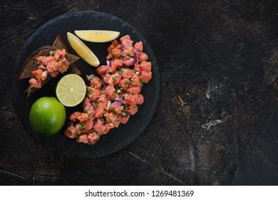 Salmon tartar served on a stone slate tray, flatlay on a dark brown stone background, copyspace