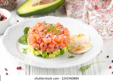 Salmon tartare with red onion, avocado, arugula and bread toast. Beautiful snack, dietary food, appetizer for Christmas holiday. On white wooden background