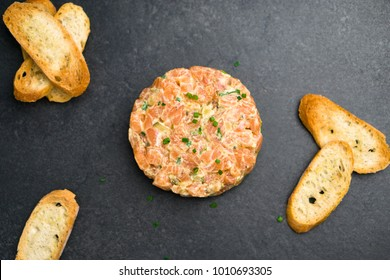 Salmon tartare top view, a dish made with chopped fresh raw salmon fish, avocado, tartar sauce and crackers or bread. This healthy dish is often served as appetizer in fine dining restaurants.