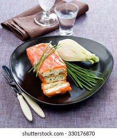 Salmon Terrine with Fennel smoke on the elegant black plate with green onions on a tablecloth made of linen