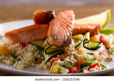 Salmon with tomato couscous, zucchini and lime