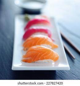 salmon and tuna nigiri on white plate