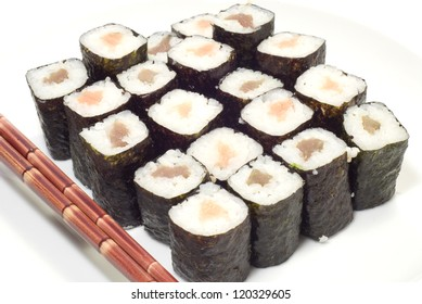 Salmon and tuna sushi rolls and red chopsticks isolated on white.