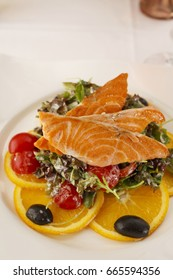 Salmon with vegetables arranged on a plate, Traditional dish in elegant setting, Selective focus with soft light