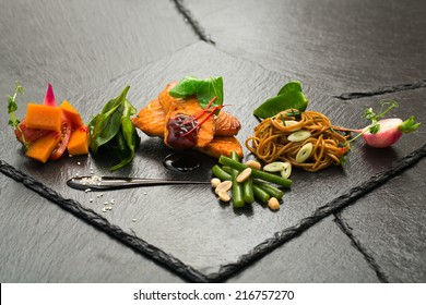 salmon with vegetables on black slate