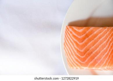 Salmon in white dish on white blackground.